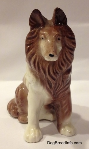 A brown and white porcelain Rough Collie figurine that is in a sitting pose. The figurine has its ears up.