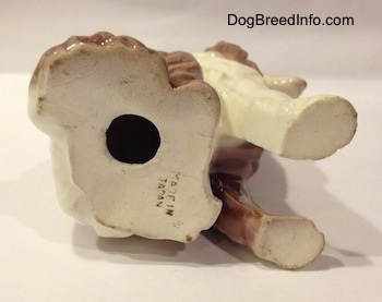 The underside of a brown and white porcelain Rough Collie figurine that has a hole in the bottom.