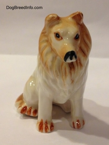 A tan and white bone china Rough Collie figurine. The figurine has poor facial details.