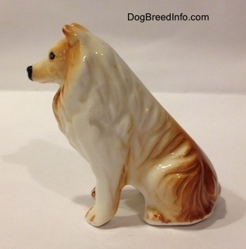 The right side of a tan and white bone china Rough Collie figurine. The figurine has tan on top of its paws.