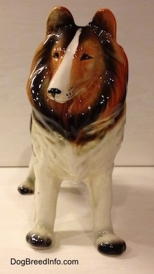 A black, brown and white highly detailed ceramic Rough Collie figurine. The figurine has black whisker dots around its muzzle.