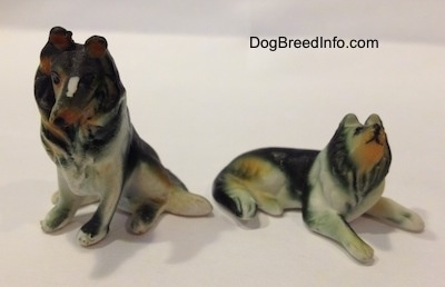 Two Rough Collie figurines, one is in sitting position and the other is lying down.