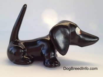The right side of a black Dachshund figurine. The figurine has a long nose.