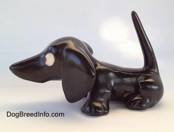 The left side of a black Dachshund figurine. The figurine has a very long tail that is in the air.
