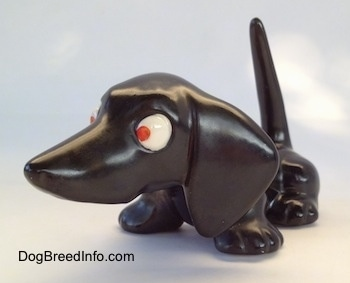 The front left side of a black Dachshund figurine. The figurine has red eyes.