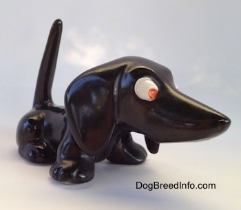 The front right side of a black Dachshund figurine. Thefigurine has no mouth and it has big ears.
