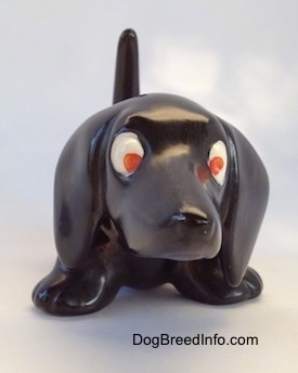 A black Dachshund figurine. The figurine has big paws, big ears and red eyes.
