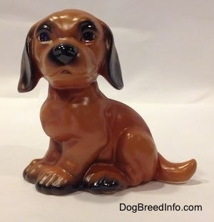 The left side of a brown with black Dachshund puppy in a sitting pose figurine. The figurine has large eyebrows.