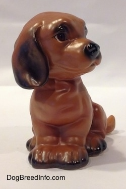 A brown with black Dachshund puppy in a sitting pose figurine. The figurines paws are connected together.
