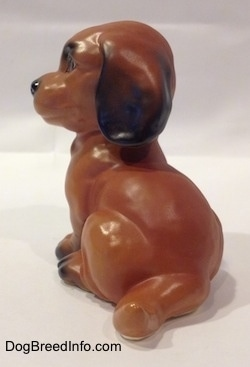 The back left side of a brown with black Dachshund puppy in a sitting pose figurine. The figurines tail is medium length relative tot he size of the figurine.