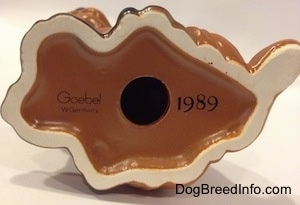 The underside of a figurine of a Dachshund puppy and it has a holde in the bottom. To the left of the hole is a number - 1989 - and to the right is the word logo of Goebel W.Germany.