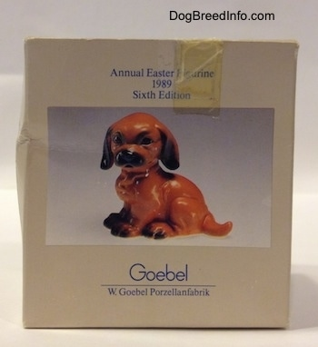 A box with a photo of a figurine that is a Dachshund puppy in a sitting pose.