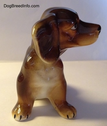 A ceramic brown with tan Dachshund figurine. The figurine has big ears and a white chest. The figurine has big paws with black nails on it.