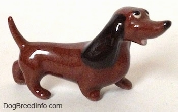 The right side of a brown Dachshund figurine named 'Dachsie' that is from 'Disney's The Lady and the Tramp'. The figurines ears are long and black.
