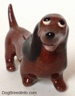 A figurine of a brown Dachshund named 'Dachsie'. The figurine has an open mouth and short appendages.