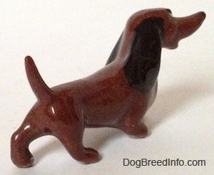 The back right side of a brown figurine that has a long nose, long body and short legs.