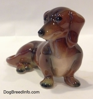 A brown and black Dachshund figurine in a sitting pose.
