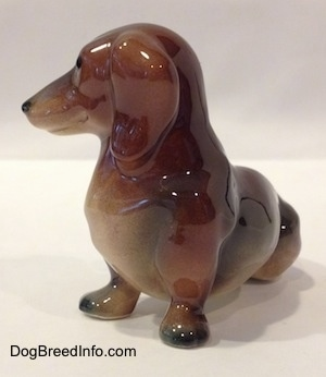 The front left side of a brown and black Dachshund figurine in a sitting pose. The figurine has black tipped paws.