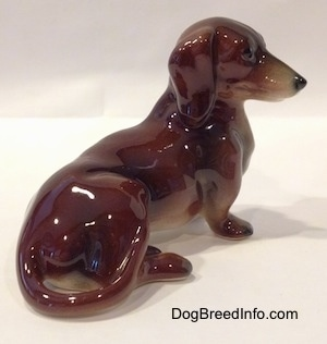 The right side of a figurine of a brown and black Dachshund in a sitting pose. The figurine has a detailed face.