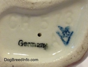 Close up - The underside of a Dachshund figurine. On the underside there are two stamps and an engraving. The stamps are Germany and the stamp of Goebel W.Germany. The engraving is of the letter/number combination - CH 573 A.
