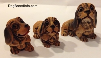 The front right side of three different plastic Dachshund figurines. The figurine have smiles on there faces.