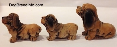 The left side of three different cartoon like plastic Dachshund figurines. All of the figurines have large paws and short legs.