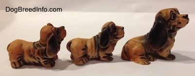 The right side of three different plastic cartoon like Dachshund figurines. The figurines are varying in sizes.