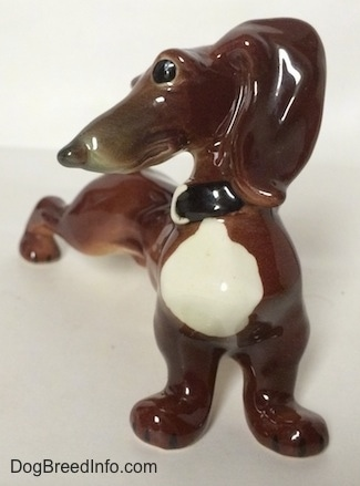 A brown with white Dachshund figurine in a strecthing pose. The figurine has big black circles for eyes.