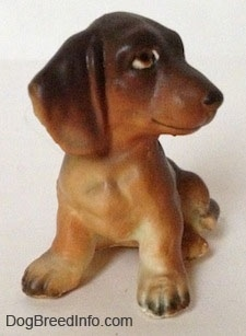 A brown with tan Dachshund puppy in a sitting pose figurine. The figurine has a detailed body, it has big paws with black nails.