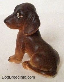 The back left side of a brown with tan Dachshund puppy in a sitting pose figurine. The figurine has a long body and it has a long tail across its leg.