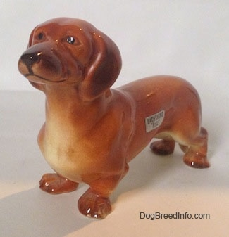 The front left side of a brown Dachshund figurine that is in a standing pose. The figurine has great face details.