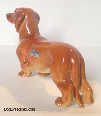 The back left side of a brown Dachshund figurine that is in a standing pose. The figurines ears are attached to its neck.