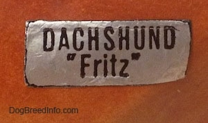 Close up - A sticker on the side of a Dachshund figurine that reads - DACHSHUND 'Fritz'