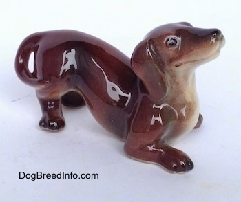 The front right side of a figurine that is of a brown with tan Dachshund in a play bow pose. The figurine has black circles for eyes.