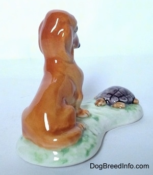 The back right side of a figurine of a brown Dachshund that is sitting across and looking down at a tortoise in front of it. The Tortoise figurine is looking at the Dachshund in front of it.