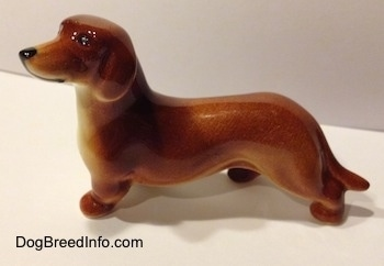 The left side of a brown Dachshund figurine. The figurine has a small ear that is hard to differentiate from its body.