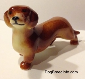 The front left side of a figurine of a brown Dachshund. The figurine has small black circles for eyes.