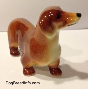 A brown Dachshund figurine. The figurine has short legs and brown paws.