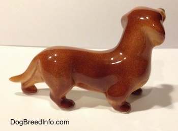 The right side of a brown Dachshund figurine. The figurine has a long body.