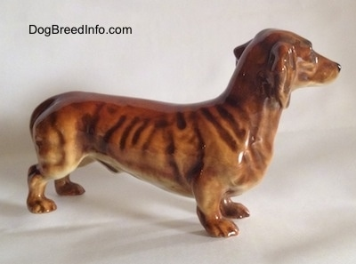 The right side of a brown Dachshund figurine. The figurine has a long body and it has fine details.