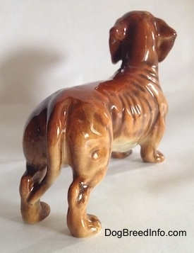 The back right side of a brown Dachshund figurine. The figurine has short detailed legs and paws.