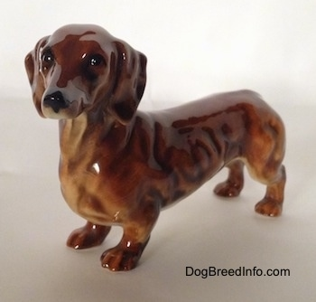 A brown Dachshund figurine. The figurine has fine face details.