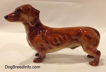 The left side of a figurine of a brown Dachshund. The figurine has long ears and it is attached to its body.