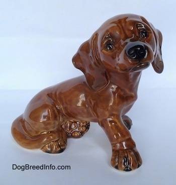 The right side of a brown Dachshund puppy figurine in a sitting pose. The figurine has black circles for eyes.
