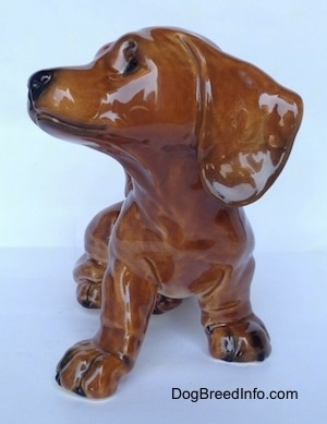 A figurine of a brown Dachshund puppy figurine that is in a sitting pose. The figurine has long ears.