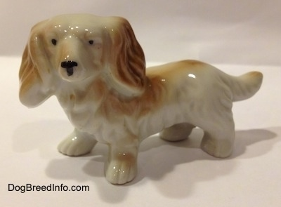 The left side of a white with tan porcelain long haired Dachshund figurine. The figurine has long hair details and it has tiny black circles for eyes.