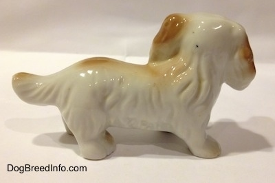 The right side of a white with tan porcelain long haired Dachshund figurine. The figurine has big ears with hair details.