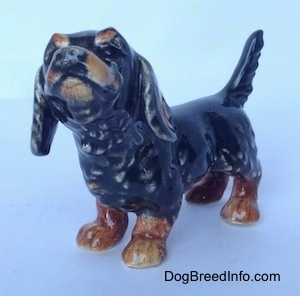 The front left side of a figurine of a black and brown Dachshund in a standing pose with its tail up. The figurine has a lot of detail in its face.