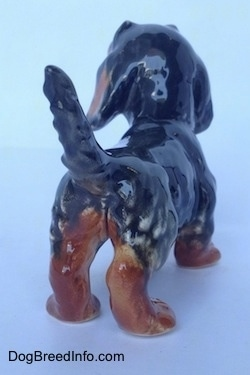 The back right side of a black and brown Dachshund figurine in a standing pose with its tail up. The figurine is glossy.