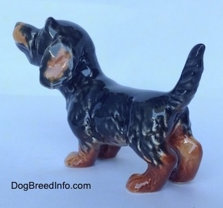 The back left side of a figurine of a black and brown Dachshund in a standing pose with its tail up. The figurine has detailed hair shapings.
